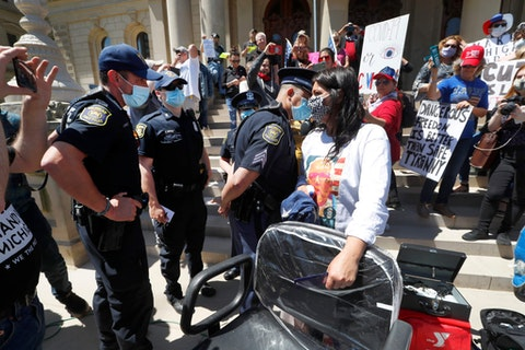 A Michigan State Police trooper talks with hair stylist Jody Hebberd while giving free haircuts at the State Capitol during a rally in Lansing, Mich., Wednesday, May 20, 2020. Barbers and hair stylists are protesting the state's stay-at-home orders, a defiant demonstration that reflects how salons have become a symbol for small businesses that are eager to reopen two months after the COVID-19 pandemic began. (AP Photo/Paul Sancya)
