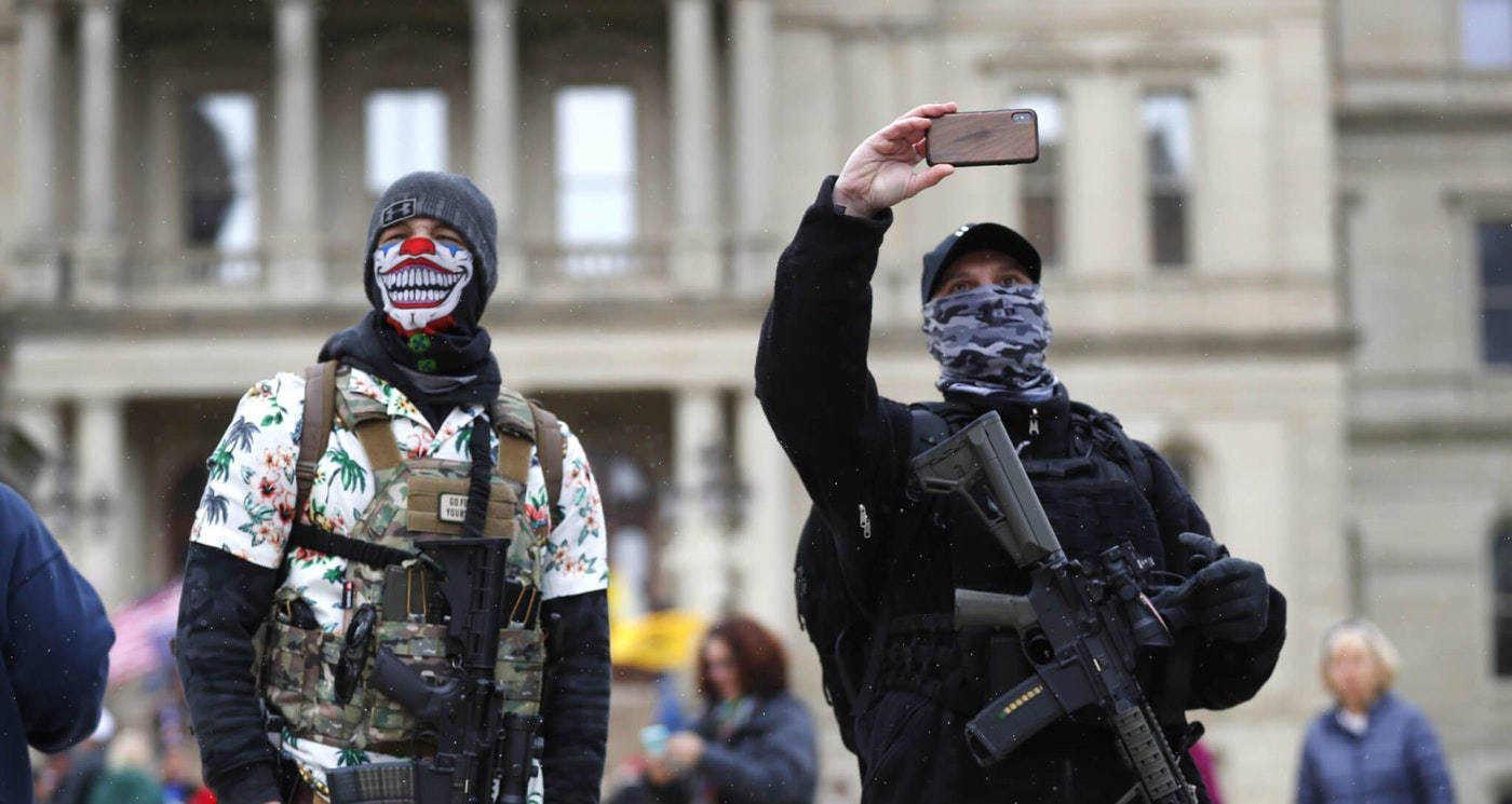 Protesters with rifles watch outside the State Capitol in Lansing, Mich., Wednesday, April 15, 2020. Flag-waving, honking protesters drove past the Michigan Capitol on Wednesday to show their displeasure with Gov. Gretchen Whitmer's orders to keep people at home and businesses locked during the new coronavirus COVID-19 outbreak. (AP Photo/Paul Sancya)
