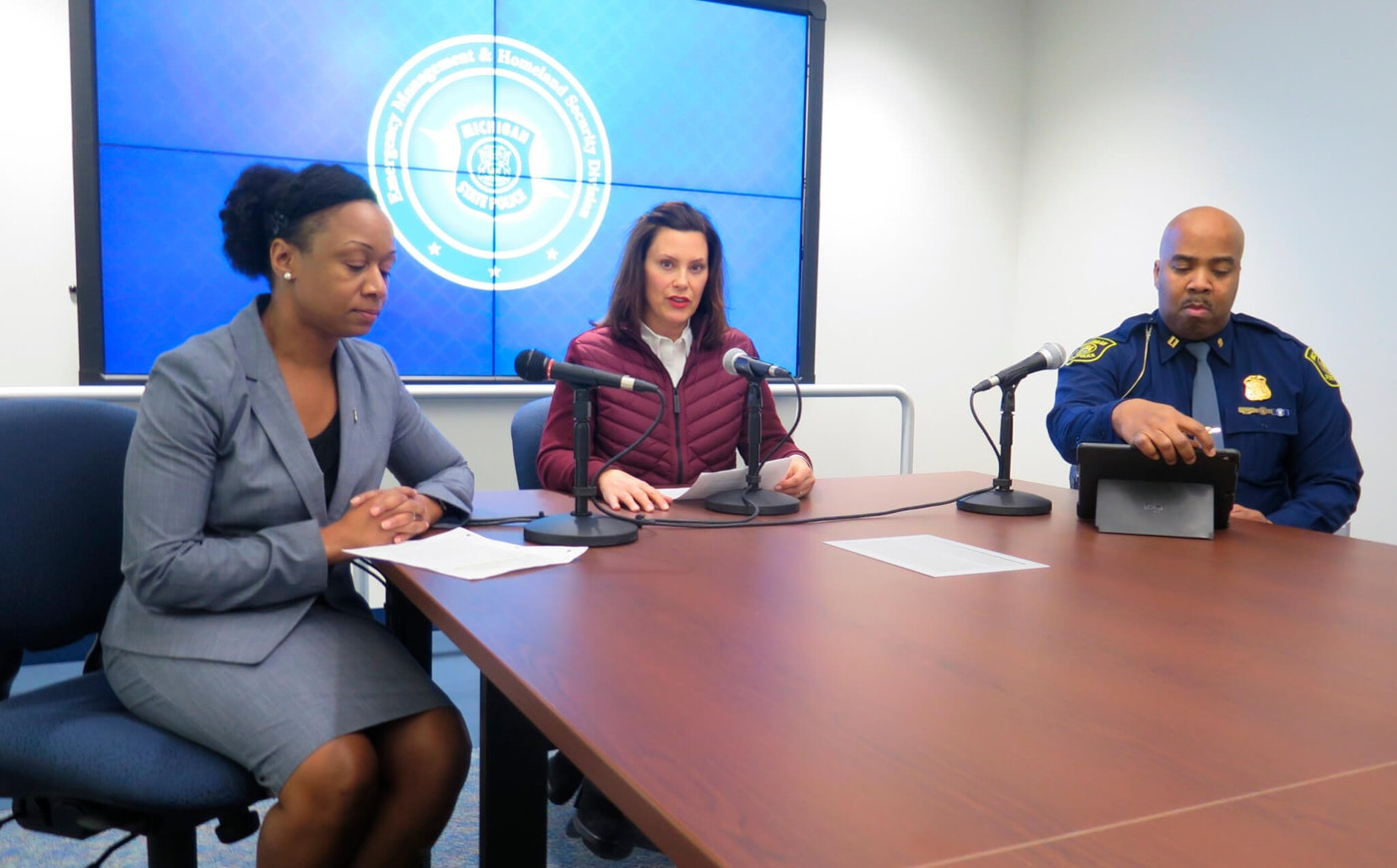 """FILE - In this March 10, 2020 file photo, Michigan Gov. Gretchen Whitmer, center, announces the state's first two cases of coronavirus, during a news conference in Windsor Township, Mich. At left is Dr. Joneigh Khaldun, the state's chief medical executive, and at right is Capt. Emmitt McGowan, deputy state director of emergency management and homeland security. Dr. Khaldun, announced Monday, May 4, 2020, that Michigan hospitals and physicians have """"broad discretion"""" to decide whether to continue delaying procedures during the pandemic. (AP Photo/David Eggert File)"""