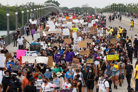 Protesters march on the MacArthur Bridge across the Detroit River during a rally in Detroit, Friday, June 5, 2020 over the death of George Floyd, a black man who died in police custody in Minneapolis on Memorial Day. (AP Photo/Paul Sancya)