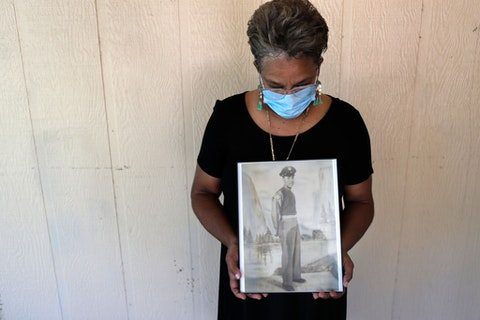 In this May 18, 2020, file photo, Belvin Jefferson White poses with a portrait of her father Saymon Jefferson at Saymon's home in Baton Rouge, La. Belvin recently lost both her father and her uncle, Willie Lee Jefferson, to COVID-19.  African Americans are disproportionately likely to say a family member or close friend has died of COVID-19 or respiratory illness since March, according to a series of surveys conducted since April that lays bare how black Americans have borne the brunt of the pandemic. (AP Photo/Gerald Herbert, File)