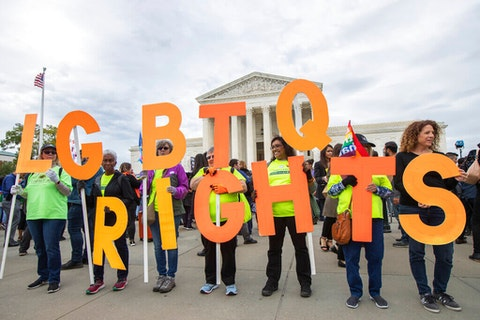 In this Oct. 8, 2019, file photo, supporters of LGBTQ rights hold placards in front of the U.S. Supreme Court in Washington. The Supreme Court has ruled that a landmark civil rights law protects gay, lesbian and transgender people from discrimination in employment. It's a resounding victory for LGBT rights from a conservative court. (AP Photo/Manuel Balce Ceneta, File)