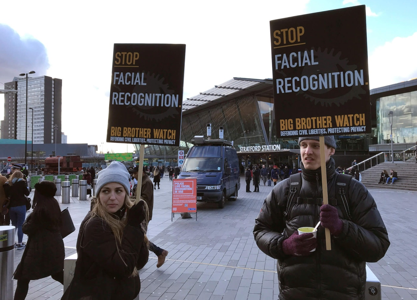 In this Feb. 11, 2020, file photo, Silkie Carlo, left, demonstrates in front of a mobile police facial recognition facility outside a shopping centre in London. A Black man who says he was unjustly arrested because facial recognition technology mistakenly identified him as a suspected shoplifter is calling for a public apology from Detroit police. And for the department to abandon its use of the controversial technology. (AP Photo/Kelvin Chan, File)