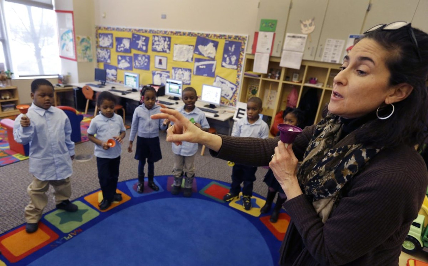 In this Feb. 25, 2014 photo, Golightly Education Center teacher Amy Andersen-Prebo leads her class in a hand bell song in Detroit. After years without comprehensive sports and arts/music programs, those are now being restored at all DPS elementary and middle schools, thanks in part to foundation grants. (AP Photo/Carlos Osorio)