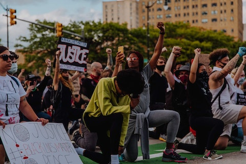 Protesters kneel in silence to recognize the murder of George Floyd, an unarmed Black man, by police.