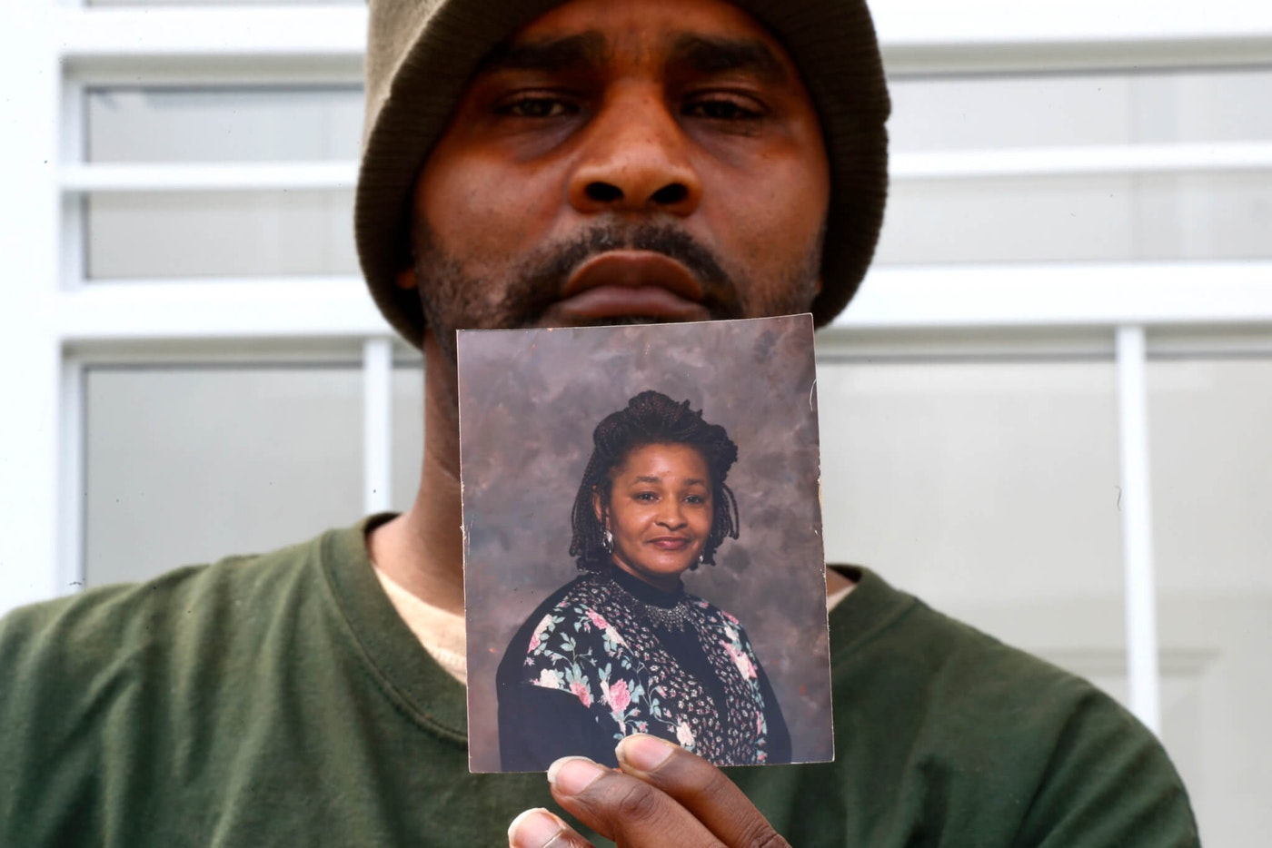 Jamon Jordan poses with a photo of his mother, Jacquelynne Jordan, in Detroit, Friday, April 24, 2020. Jamon Jordan could not mourn his mother in the traditional way. At Jacquelynne Jordan's memorial in early April, there were just seven people. No hugs. No traditional dinner where family members could gather to honor the 66-year-old matriarch's memory after she died from the new coronavirus. (AP Photo/Paul Sancya)