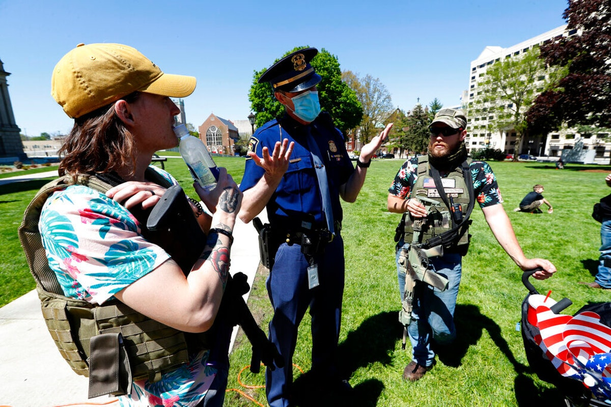 Men with rifles talk with a Michigan State Police trooper at the State Capitol during a rally in Lansing, Mich., Wednesday, May 20, 2020. Barbers and hair stylists were protesting the state's stay-at-home orders, a defiant demonstration that reflected how salons had become a symbol for small businesses that were eager to reopen two months after the COVID-19 pandemic began. (AP Photo/Paul Sancya)