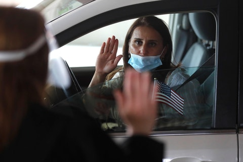 In this Friday, June 26, 2020 photo, U.S. District Judge Laurie Michelson, left, administers the Oath of Citizenship to Hala Baqtar during a drive-thru naturalization service in a parking structure at the U.S. Citizenship and Immigration Services headquarters on Detroit's east side. The ceremony is a way to continue working as the federal courthouse is shut down due to Coronavirus. The U.S. has resumed swearing in new citizens but the oath ceremonies aren't the same because of COVID-19 and a budget crisis at the citizenship agency threatens to stall them again.  (AP Photo/Carlos Osorio)