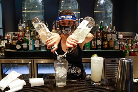 A bartender mixes a drink while wearing a mask and face shield at Slater's 50/50 in Santa Clarita, CA. Bars have been tied to numerous recent outbreaks across the nation. (AP Photo/Marcio Jose Sanchez)