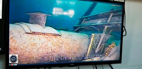 This June 2020 file photo, shot from a television screen provided by the Michigan Department of Environment, Great Lakes, and Energy shows damage to anchor support EP-17-1 on the east leg of the Enbridge Line 5 pipeline within the Straits of Mackinac in Michigan. Michigan sought a pledge Friday, July 17, 2020 from Enbridge Inc. to cover costs that would arise if oil were to leak from its dual pipelines that extend across a channel linking two of the Great Lakes.  (Michigan Department of Environment, Great Lakes, and Energy via AP File)