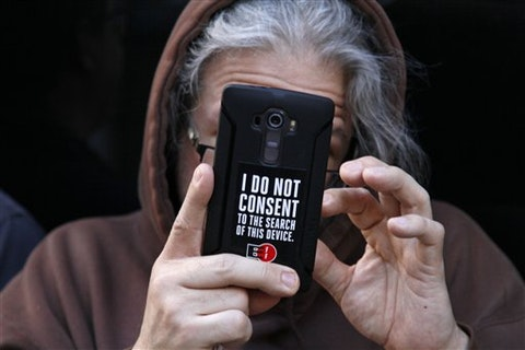 A person holds up their phone during a rally in support of data privacy outside the Apple store Tuesday, Feb. 23, 2016, in San Francisco. (AP Photo/Eric Risberg)