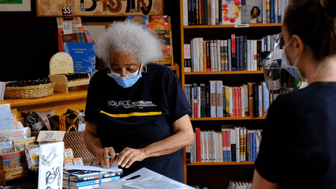 Janet Webster Jones, owner of Source Booksellers in Detroit, helps a customer who stopped by to pick up an online order. (Photo by Adam Fox-Long)