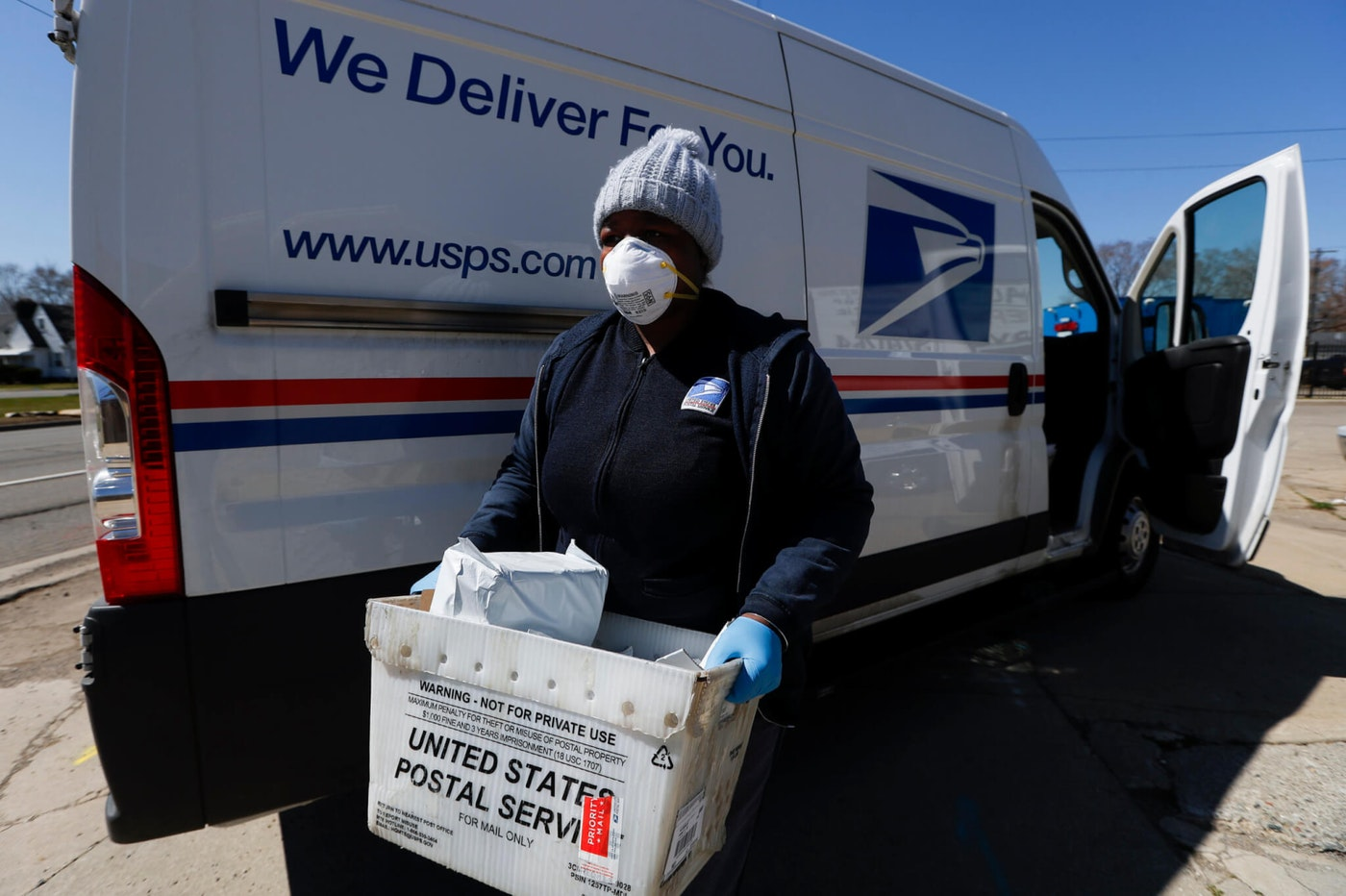 A United States Postal worker makes a delivery with gloves and a mask in Warren, MI. AP Photo/Paul Sancya)