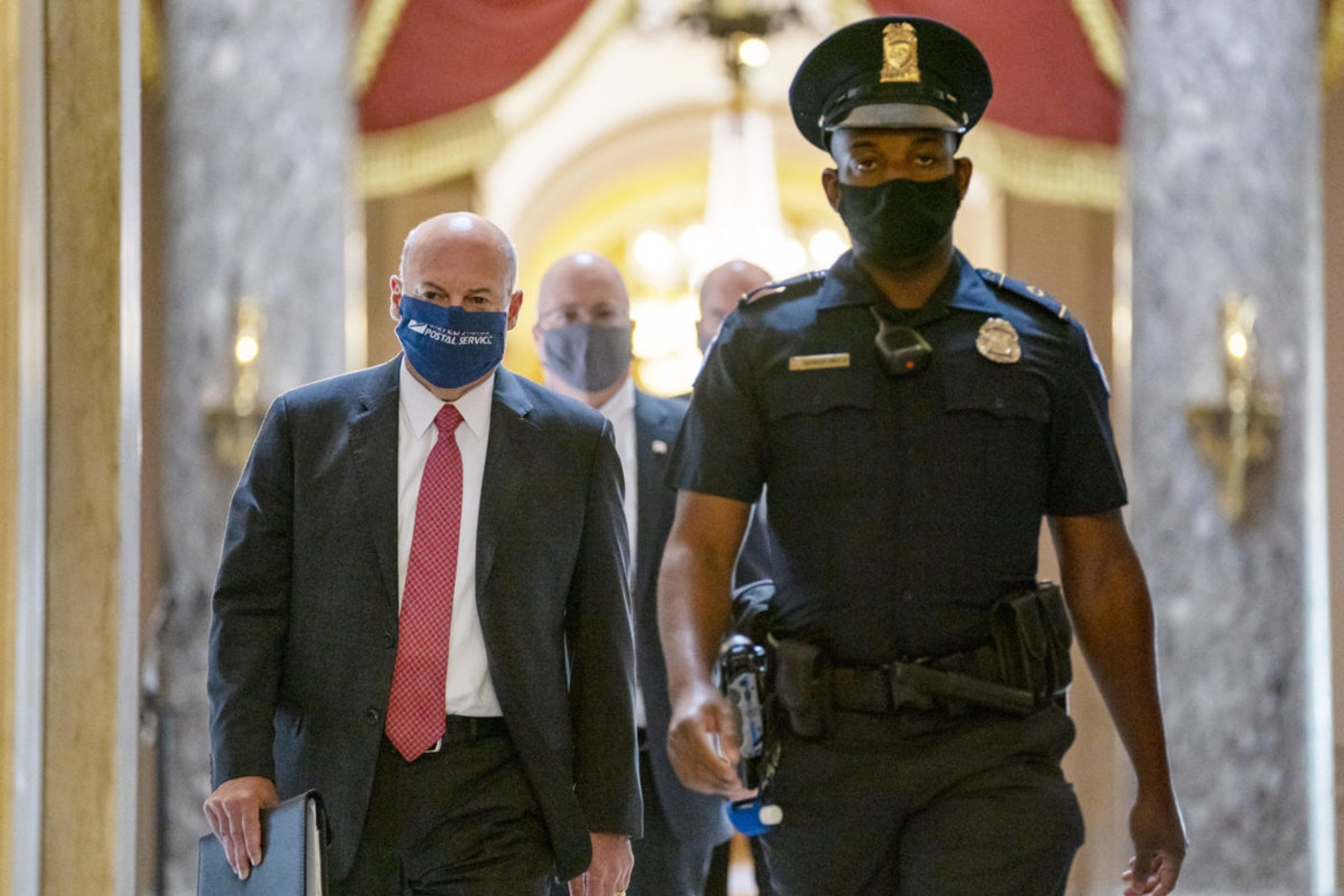 FILE - In this Aug. 5, 2020, file photo Postmaster General Louis DeJoy, left, is escorted to House Speaker Nancy Pelosi's office on Capitol Hill in Washington. The Post Office has lost money for years, though advocates note it's a government service rather than a profit-maximizing business. In June, President Donald Trump appointed DeJoy, a Republican donor and logistics company executive, as the country's new postmaster general and tasked him with trying to make the postal service more profitable.  (AP Photo/Carolyn Kaster, File)