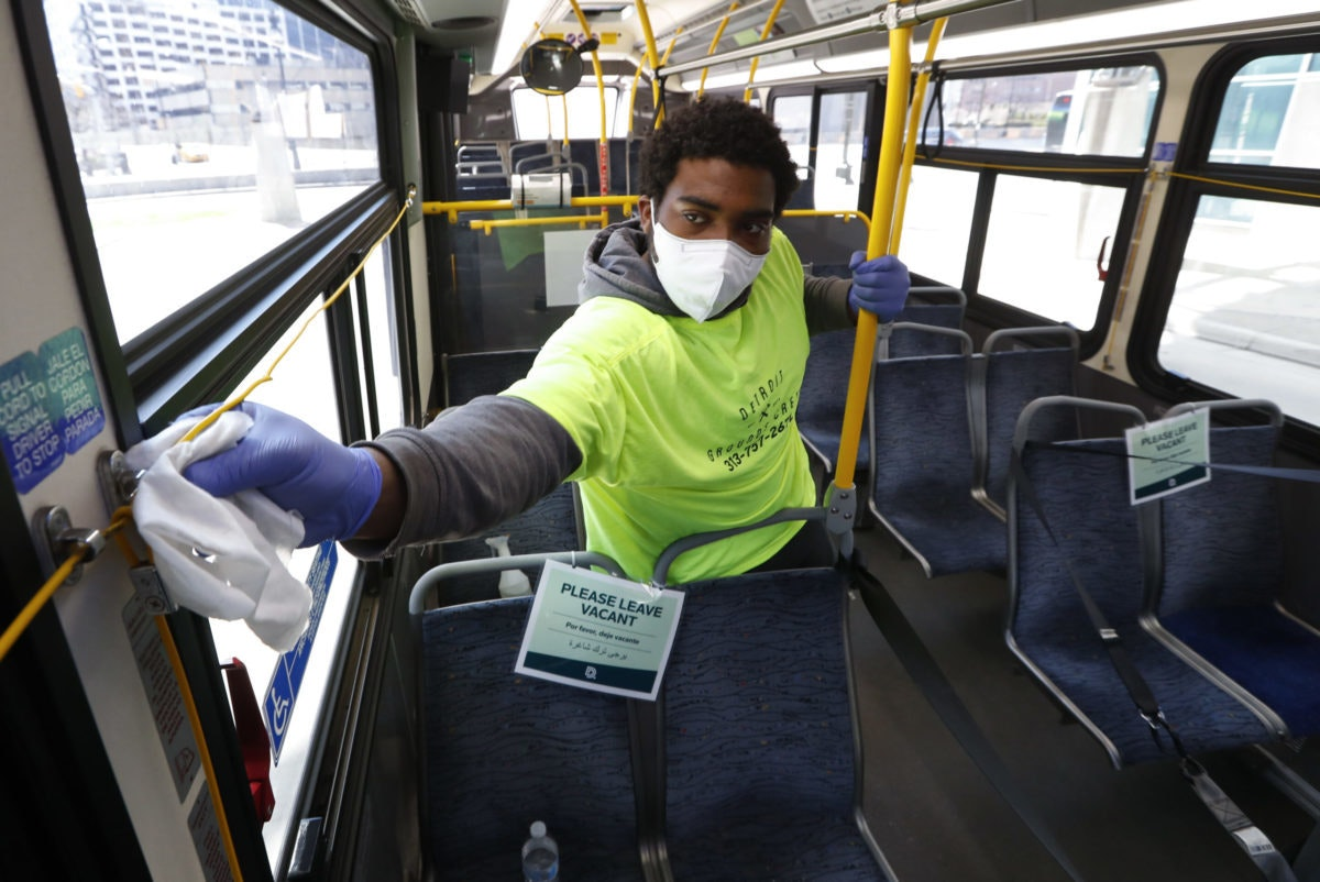 Robert Day works on disinfecting surfaces on a bus in Detroit, Wednesday, April 8, 2020. Detroit buses will have surgical masks available to riders starting Wednesday, a new precaution the city is taking from the new coronavirus COVID-19. (Photo provided by AP)