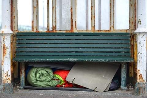 A homeless person's sleeping bags and bedding under a bench. Photo via Shutterstock