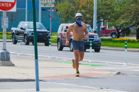 A jogger is shown running with a handkerchief mask on in Detroit, Michigan as the coronavirus (COVID-19) global pandemic and statewide stay at home orders continue. (Shutterstock)
