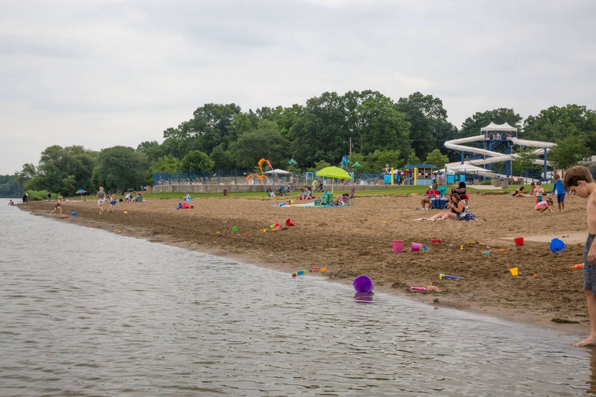 Children's toys are scattered about as several small groups of people enjoy an overcast Monday afternoon at Kensington Metropark's Martindale Beach. Shutterstock