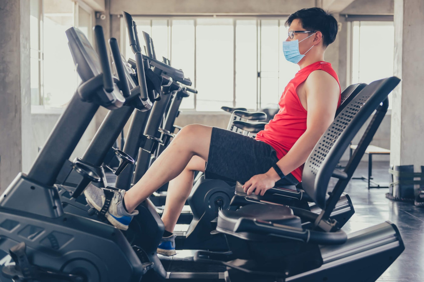 A man sits at an exercise bike at a gym. Social distancing and wellness are at the top of mind when it comes to reopening Michigan during COVID-19. (Shutterstock)