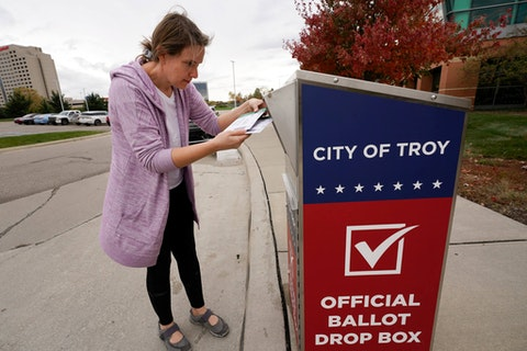 Nikki Schueller inserts her absentee voter ballot into a drop box in Troy, Mich., Thursday, Oct. 15, 2020. (AP Photo/Paul Sancya)