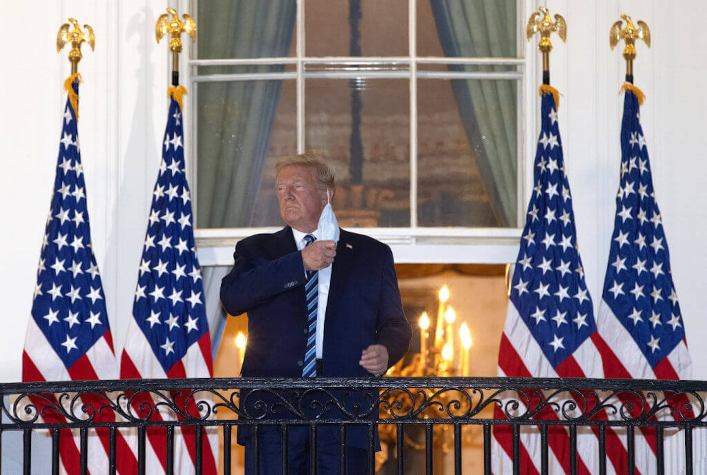 President Donald Trump removes his mask upon return to the White House from Walter Reed National Military Medical Center on October 05, 2020 in Washington, DC. Trump spent three days hospitalized for coronavirus. (Photo by Win McNamee/Getty Images)