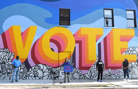 """Michigan Secretary of State Jocelyn Benson speaks in front of a newly-painted mural by artist Ndubisi Okoye, during a press conference by MichiganVoting.com Coalition members announcing """"40 Days of Early Voting"""" campaign at the ACLU of Michigan building in Detroit, Thursday, Sept. 24, 2020. (Daniel Mears/Detroit News via AP)"""
