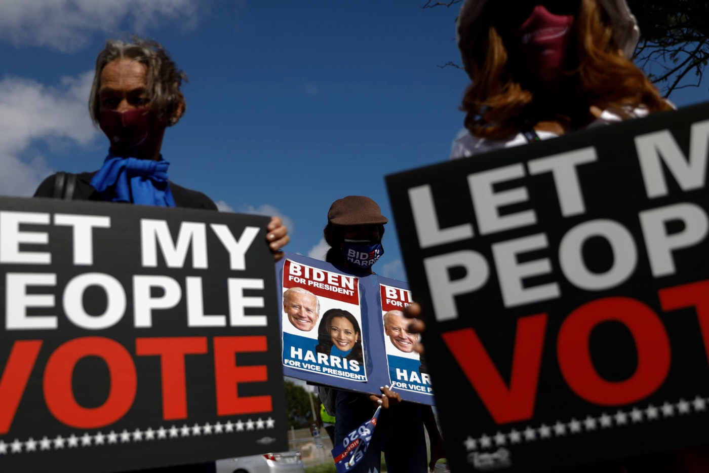 """FILE - In this Nov. 1, 2020, file photo, people carry signs supporting voting rights and former Vice President Joe Biden, during a """"Souls to the Polls"""" march in Model City, Miami. A tough road lies ahead for Biden who will need to chart a path forward to unite a bitterly divided nation and address America's fraught history of racism that manifested this year through the convergence of three national crises. (AP Photo/Rebecca Blackwell, File)"""