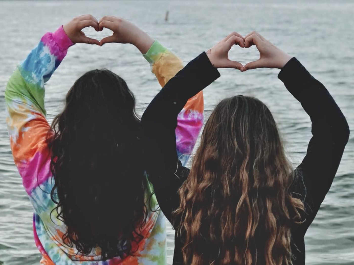 Hearts of hope, behind view of two sisters on Lake Michigan holding up their hands, making heart shapes.