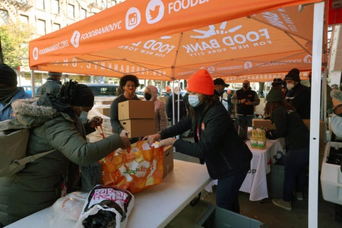 Volunteers help to give food away during a Thanksgiving food distribution event at Food Bank For New York City in the Harlem neighborhood on November 16, 2020 in New York City. Food Bank For New York City partnered with Stop & Shop and WBLS' The Steve Harvey Morning Show to give away turkeys, holiday boxes, and fresh produce to families in Harlem for Thanksgiving. (Photo by Michael M. Santiago/Getty Images)