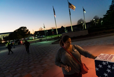 In this Tuesday, Nov. 3, 2020 file photo, Wendy Gill inserts her absentee ballot at a drop-off box as the sun sets on Election Day outside City Hall in Warren, Mich. (AP Photo/David Goldman)