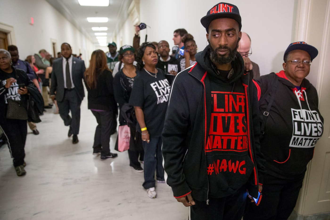 "Flint residents and supporters wear shirts in 2016 that reads ""Flint Lives Matter"" as they wait outside the room where Michigan Gov. Rick Snyder and EPA Administrator Gina McCarthy testify before a House Oversight and Government Reform Committee hearing in Washington to look into the circumstances surrounding high levels of lead found in many residents' tap water in Flint, Michigan. (AP Photo/Andrew Harnik)"