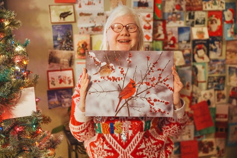 Camryn proudly displays a large, unique Christmas card sent to her through her Facebook group.