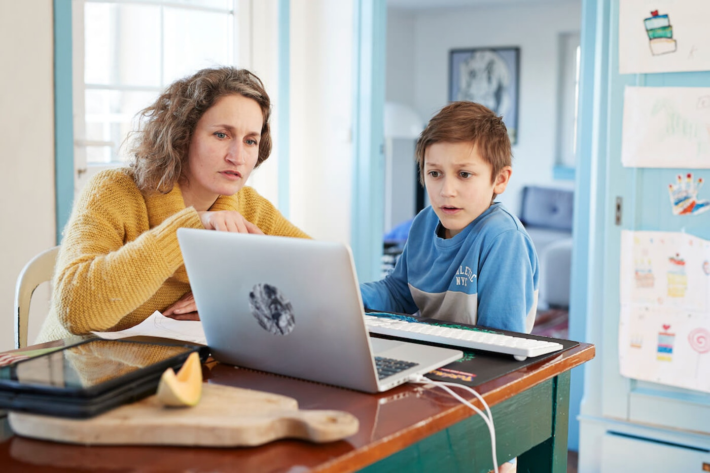 Mother homeschooling son at laptop (Image via Getty Images)