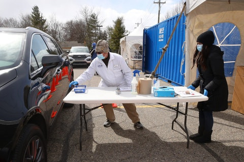 MACOMB, MICHIGAN - APRIL 21: Dimitri Bastounis of Washington Township and a Rite Aid employee prepares to give a testing swab to a drive through customer on April 21, 2020 in Macomb, Michigan. Rite Aid is opening drive through testing sites for COVID-19 all around Michigan that anyone can apply to take via their website. (Photo by Gregory Shamus/Getty Images)