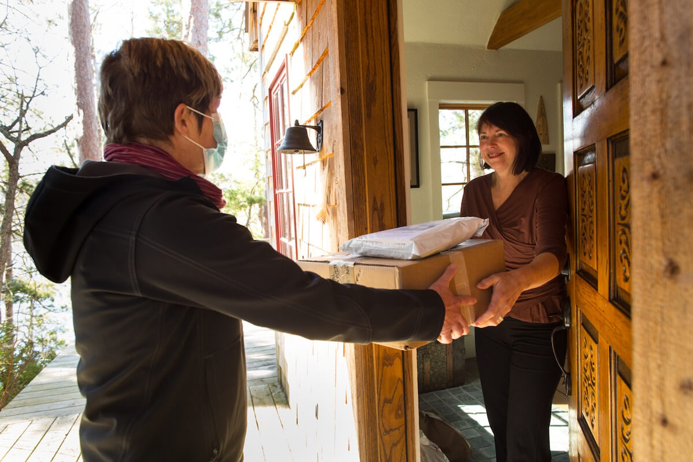 A woman accepts a package at her door from a masked delivery person. (Photo by Tim Bieber/Getty Images)