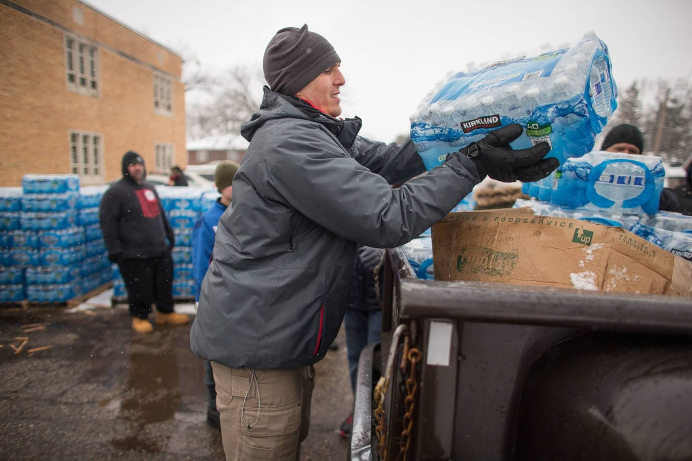 Volunteers load cases of free water into waiting vehicles at a water distribution centre at Salem Lutheran Church in Flint, Michigan, on March 5, 2016.  Flint changed its water source in April of 2014 from treated water sourced from Lake Huron as well as the Detroit River to the Flint River, but city officials allegedly failed to treat with corrosion control. The failure had a series of problems that culminated with lead contamination from aging pipes.