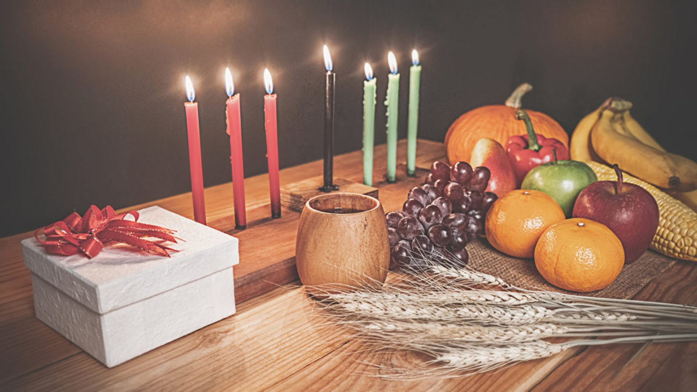 A traditional Kwanzaa table adorned with a kinara, umoja cup, fruits, and a gift. Image by Shutterstock.