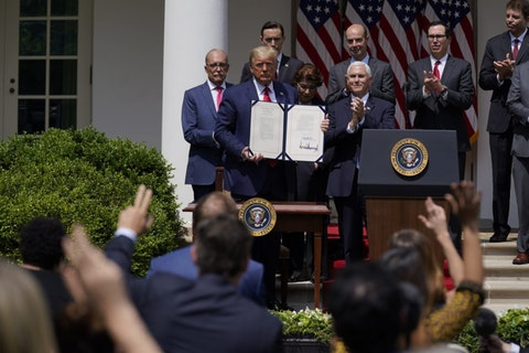FILE - In this June 5, 2020 file photo, President Donald Trump poses for a photo after signing the Paycheck Protection Program Flexibility Act during a news conference in the Rose Garden of the White House in Washington.  Thousands of minority-owned small businesses were at the end of the line in the government's coronavirus relief program as many struggled to find banks to accept their applications. Or, they were disadvantaged by the program's terms. Data from the Paycheck Protection Program analyzed by The Associated Press show many minority owners desperate for a loan didn't receive one until the PPP's last weeks.   (AP Photo/Evan Vucci, File)