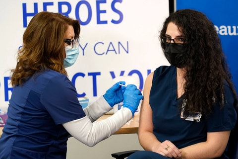 Registered nurse Paula Levesque, left, administers a second Pfizer-BioNTech COVID-19 vaccine shot to registered nurse Giulia Heiden at Beaumont Health in Southfield, Mich., Tuesday, Jan. 5, 2021.