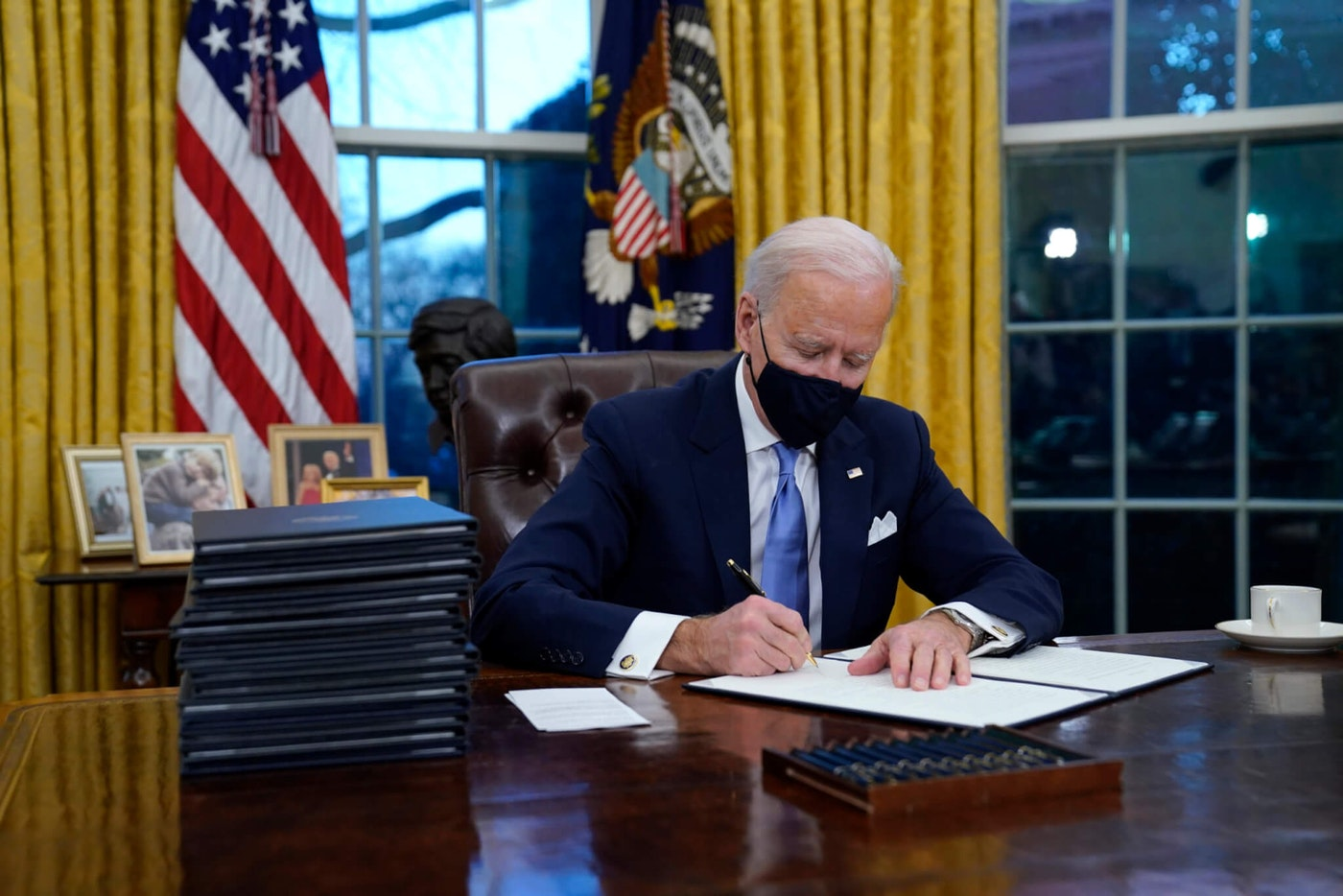 President Joe Biden signs his first executive order in the Oval Office of the White House on Wednesday, Jan. 20, 2021, in Washington.