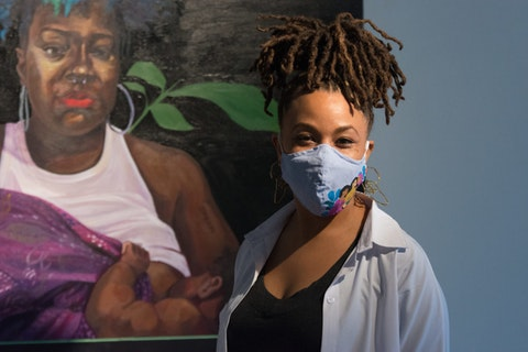 "Detroit artist and muralist Sydney G. James poses in front of one of the pieces from ""Watch Me Work—Portraits of Self"" series, currently on exhibition at the M Contemporary Art Gallery in Ferndale."