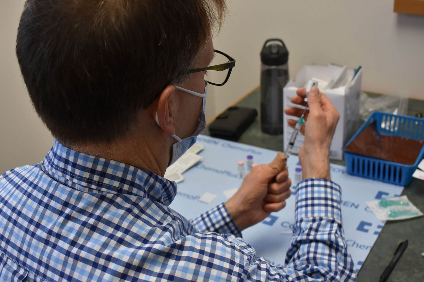 Pharmacist Mike Tiberg, retired, has returned to work to prepare COVID vaccines in Grand Traverse County.