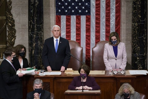 Vice President Mike Pence and Speaker of the House Nancy Pelosi stand on a podium in front of a large American flag. They are masked and solemn.