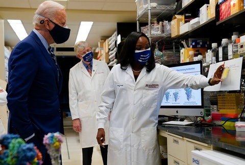 President Joe Biden listens as Kizzmekia Corbett, an immunologist with the Vaccine Research Center at the National Institutes of Health (NIH), right, speaks during a visit at the Viral Pathogenesis Laboratory at the NIH, Thursday, Feb. 11, 2021, in Bethesda, Md. NIH Director Francis Collins is at center. (AP Photo/Evan Vucci)