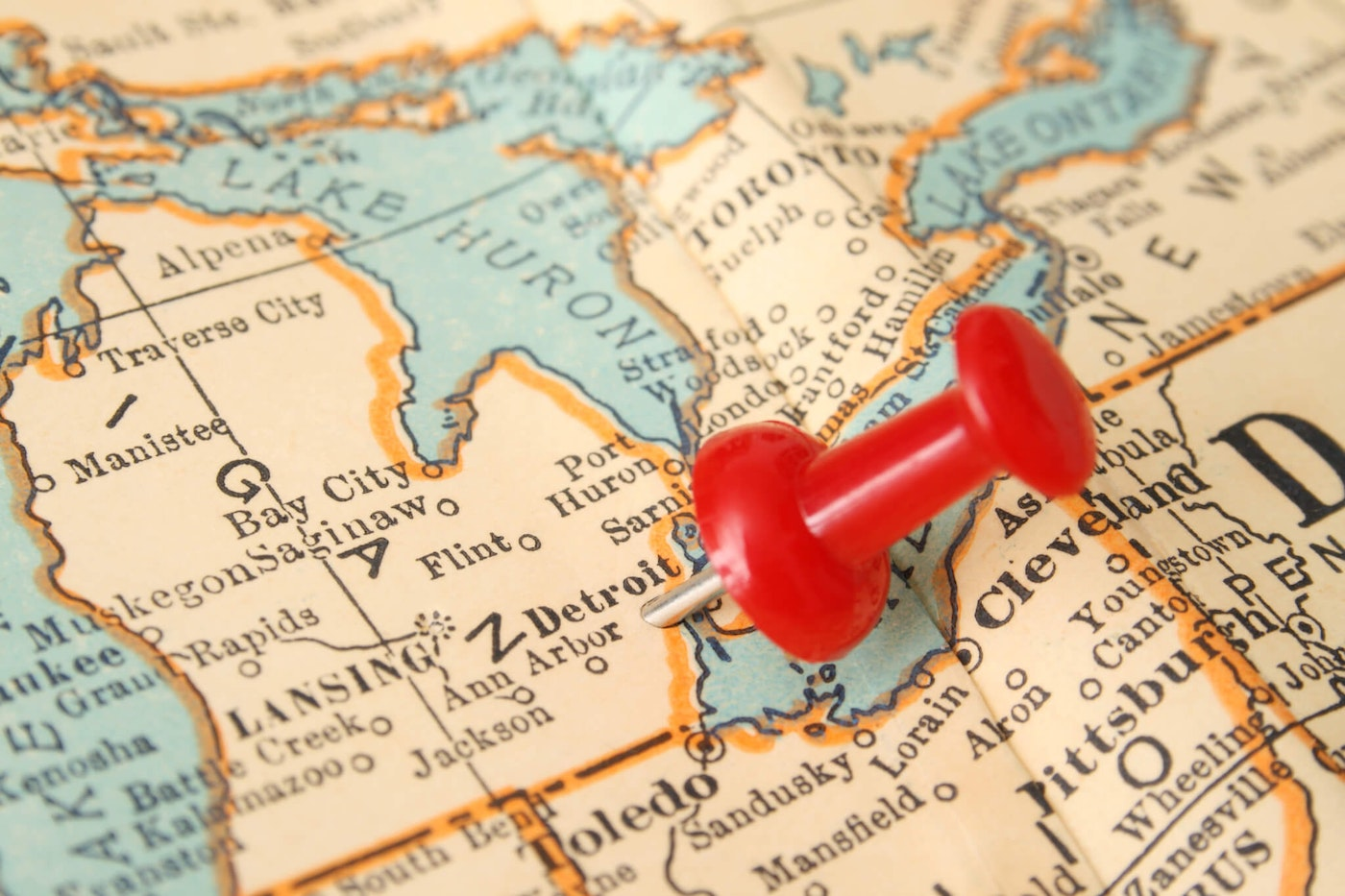 Red pushpin pointing to Detroit city in more than fifty years old map