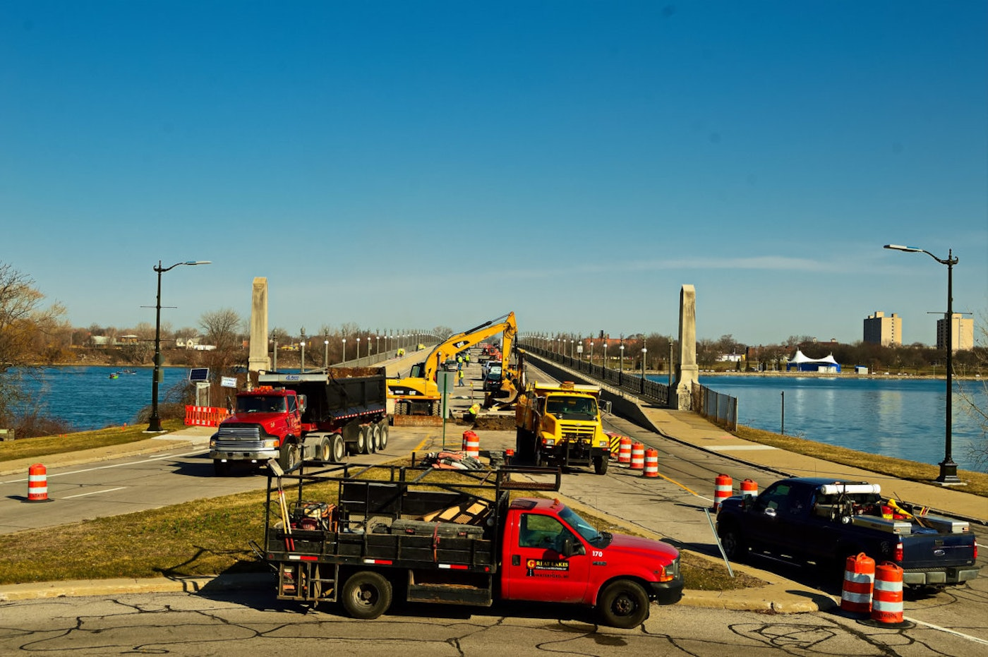 The MacArthur Bridge, which connects Jefferson Avenue to Detroit's Belle Isle, is undergoing extensive construction until fall 2018. A large group of working unrecognizable persons, along with construction barrels, and moving vehicles line the bridge.