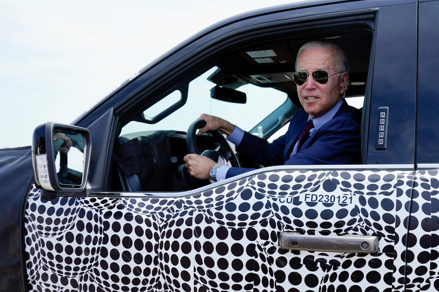 President Joe Biden stops to talk to the media as he drives a Ford F-150 Lightning truck at Ford Dearborn Development Center, Tuesday, May 18, 2021, in Dearborn, Mich..