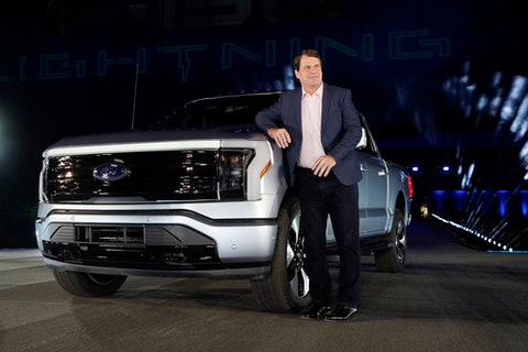 Jim Farley, Ford Motor Company's chief executive officer, stands next to the company's new Ford F-150 Lightning, Wednesday, May 19, 2021, in Dearborn, Mich. On the outside, the electric version of Ford's F-150 pickup looks about the same as the wildly popular gas-powered truck. The new truck called the F-150 Lightning can go up to 300 miles per charge, with a starting price of just under $40,000.