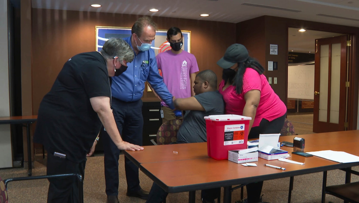 In this image made from video, a health care professional and representatives of JARC, a nonprofit dedicated to assisting those with developmental disabilities, try to persuade Noah Lebon to take a COVID-19 vaccine shot on Thursday, May 20, 2021, in Bloomfield Hills, Mich. Noah's mother, LaQuae Lebon, is standing beside her son in the vaccine clinic.