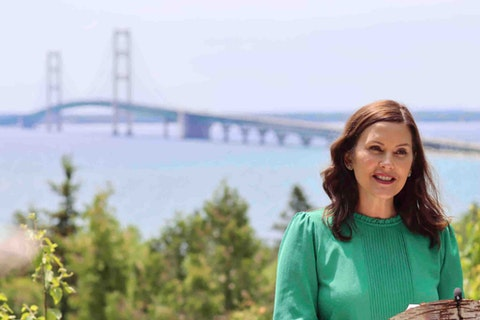 """In this June 10, 2021 photo provided by the Michigan Office of the Governor, Gov. Gretchen Whitmer speaks at Straits State Park in St. Ignace, Mich., with the Mackinac Bridge behind her. Whitmer called for spending a """"historic"""" $250 million in federal coronavirus relief aid to upgrade state parks and trails, a day after Senate Republicans announced a $1.5 billion plan to fix deteriorating local bridges across Michigan."""